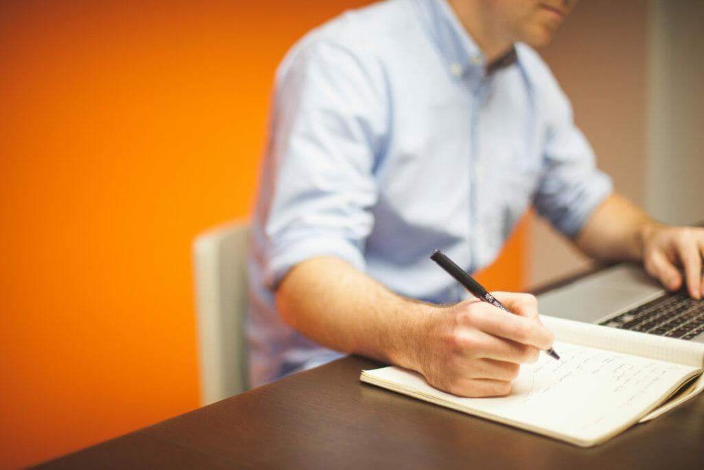 Man taking notes at his computer