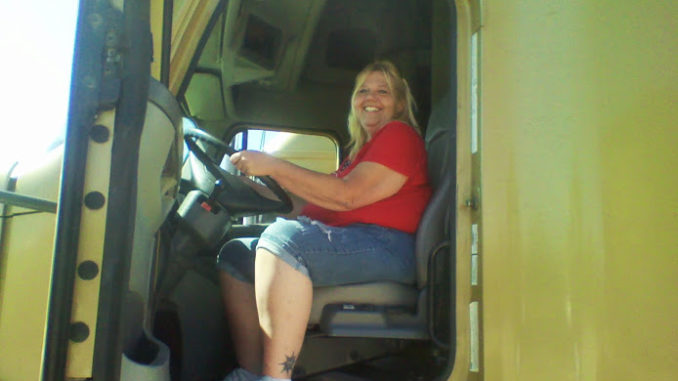 Woman truck driver in yellow truck