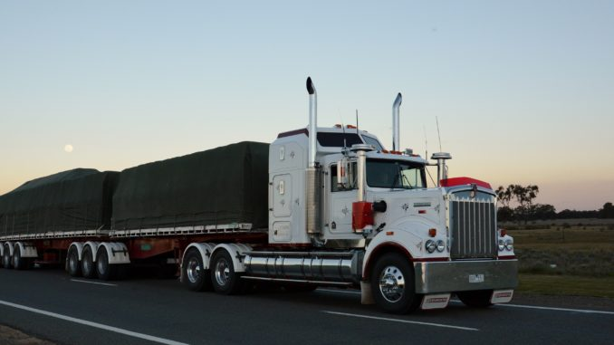 White flatbed truck driving at sunrise