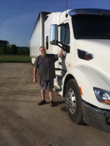 Truck driver stands next to his white tractor-trailer