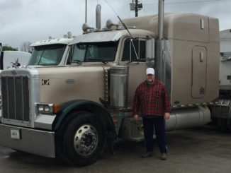 Semi-truck with driver standing in front