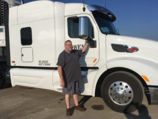 Truck driver with his white semi-truck