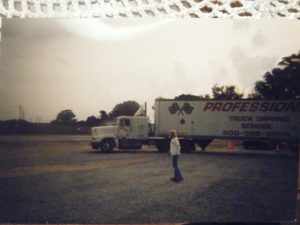 Old photo of female truck driver standing in front of her truck