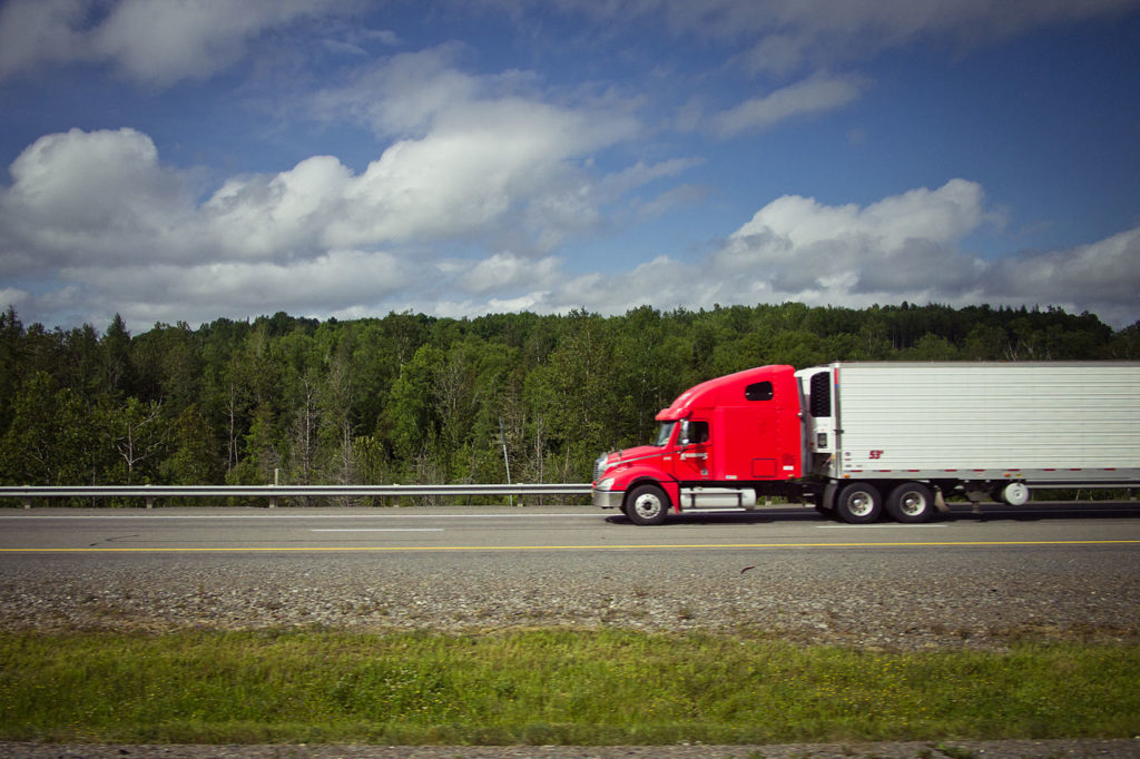 Red truck driving on a straight highway