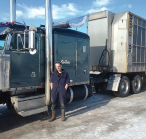 Truck driver standing in front of truck with livestock trailer
