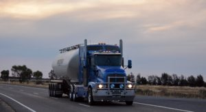 Blue tanker truck driving in the evening