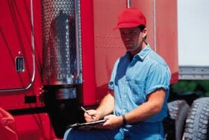 Owner-operator with clipboard and red truck