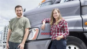 Husband and wife team truck drivers with their truck