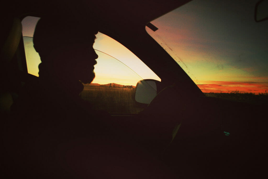 Truck driver in silhouette behind the wheel