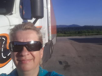 Truck driver and her truck take a photo