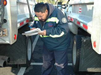 Truck Driver performs pre-trip inspection on his vehicle.