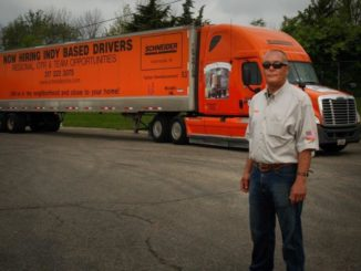 Driver stands next to his tractor-trailer