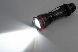 Black flashlight shining light on the ground
