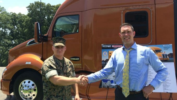 Military man shaking hands with trucking company recruiter in front of orange truck