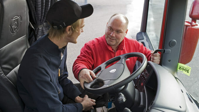 Trainer in red showing truck driver about wheel