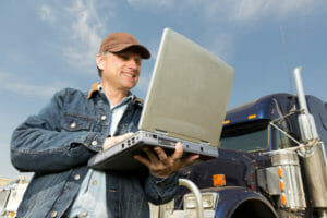 Truck driver with silver laptop in front of blue tractor-trailer