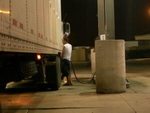 Man refuels his truck at a truck stop at night