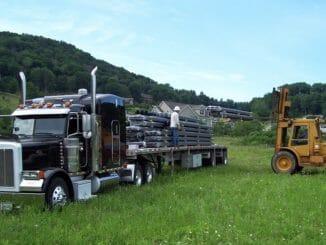 Black flatbed truck loaded in a field