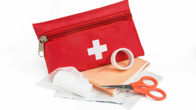 Red first aid kit with scissors and gauze