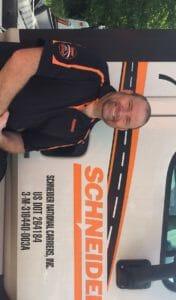 Driver standing next to a Schneider truck