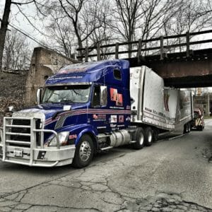 Blue tractor with a crushed trailer under a bridge