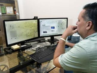 Trucking company dispatcher looking at dual computer monitors
