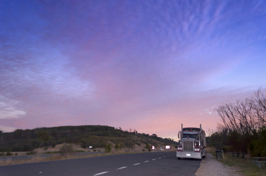 Large truck on an empty road at dusk