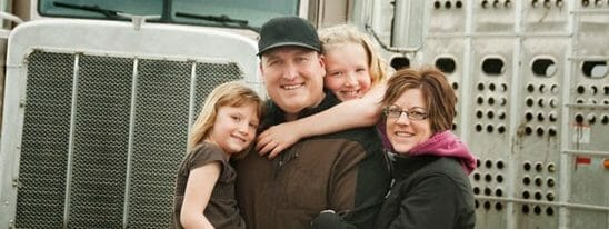 Truck driver with his family standing in front of a truck