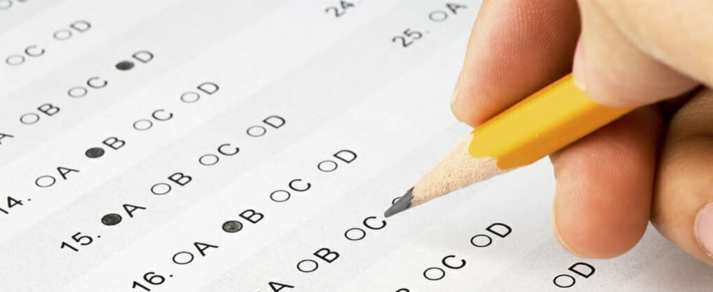 Hand filling out a multiple-choice CDL exam with a pencil