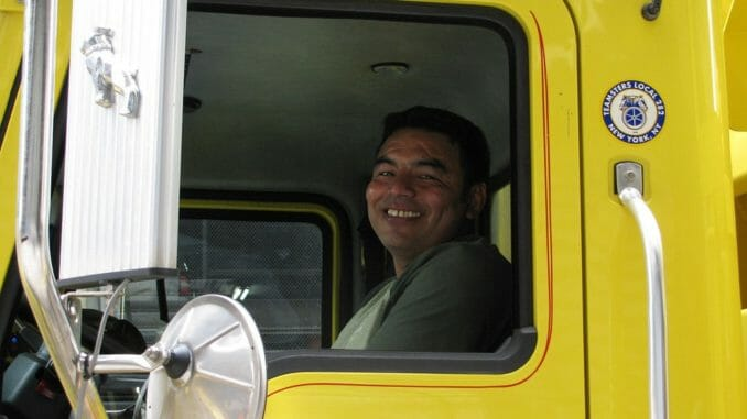 Smiling truck driver in yellow truck